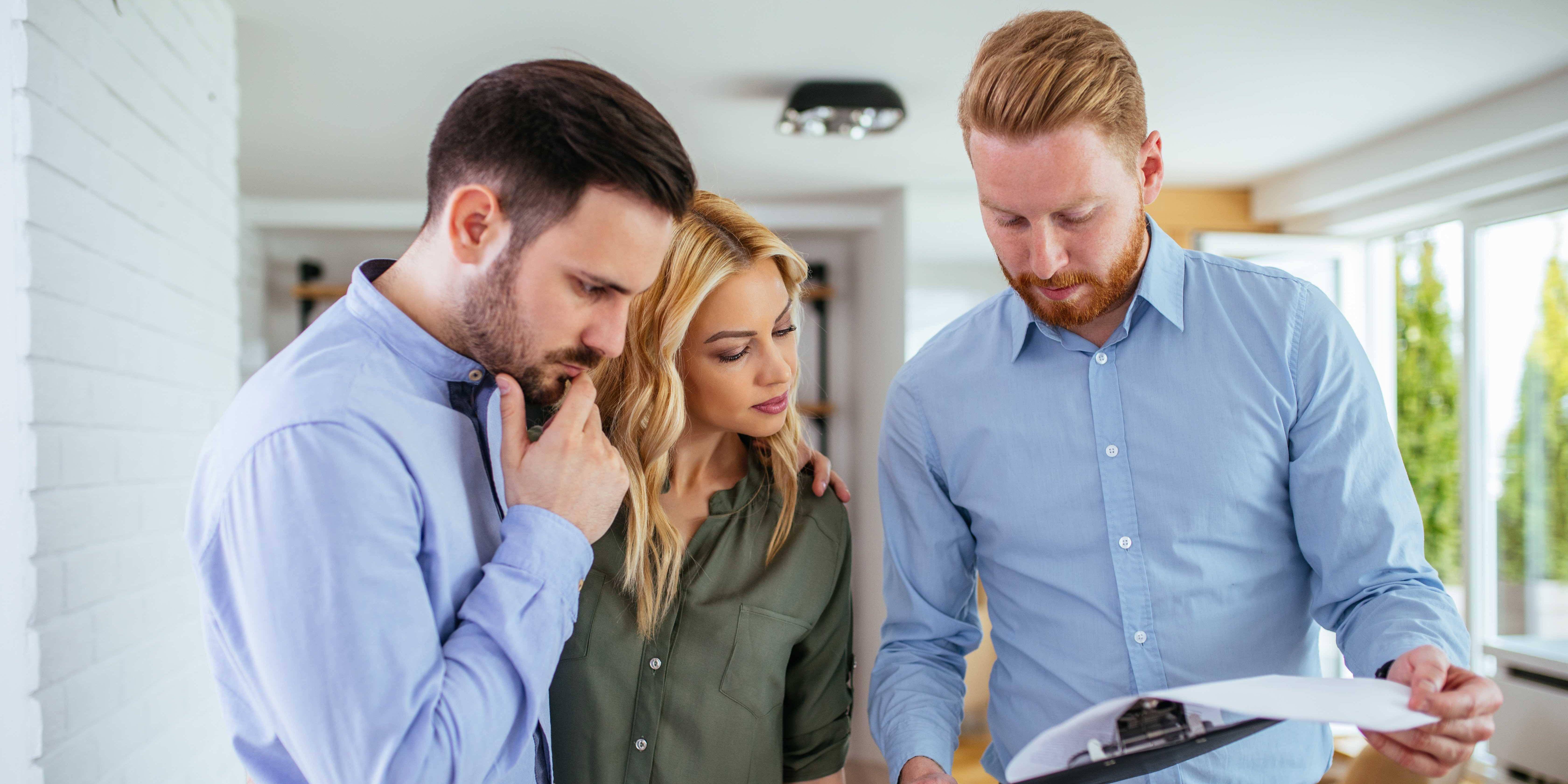 Megler og boligkjøpere ser over salgsdokumentene.
