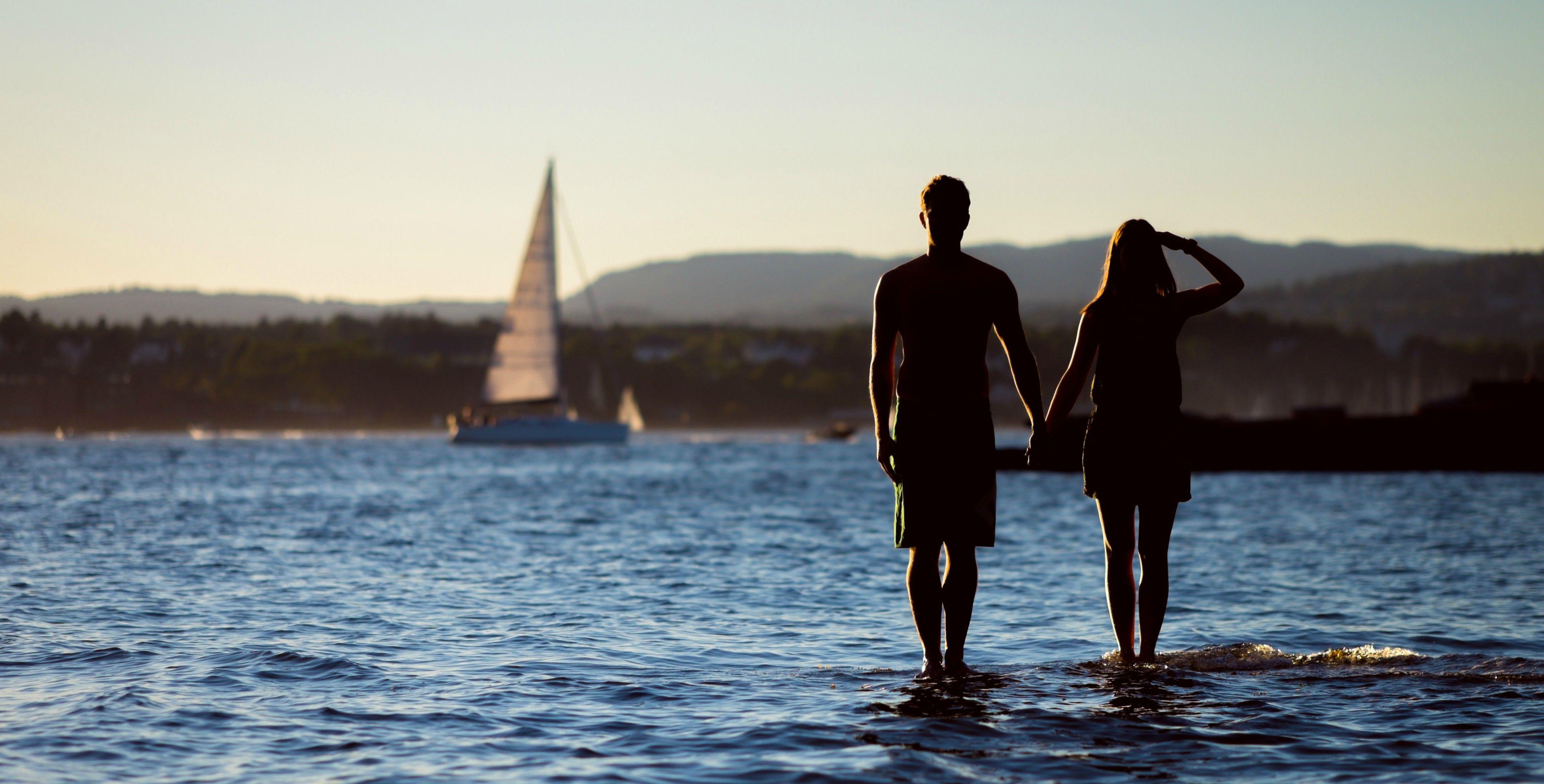 Et par står i strandkantene og ser utover havet