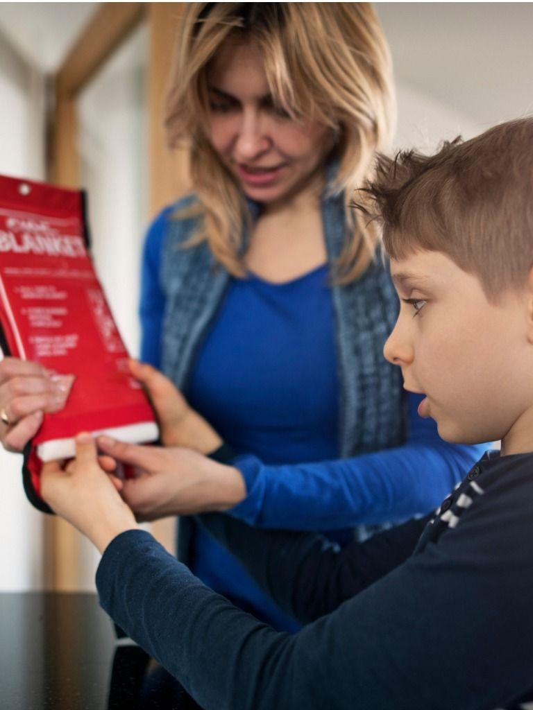 En mor förklarar hur man använder en brandfilt för sitt barn