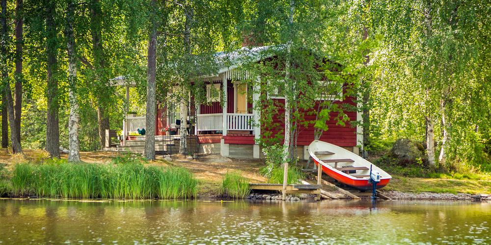Rött fritidshus bland björkar med uppdragen båt vid sidan