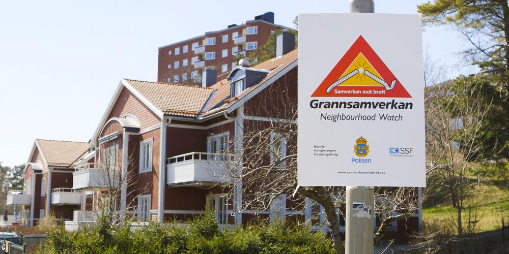 Skylt för grannsamverkan framför villa och flerfamiljshus