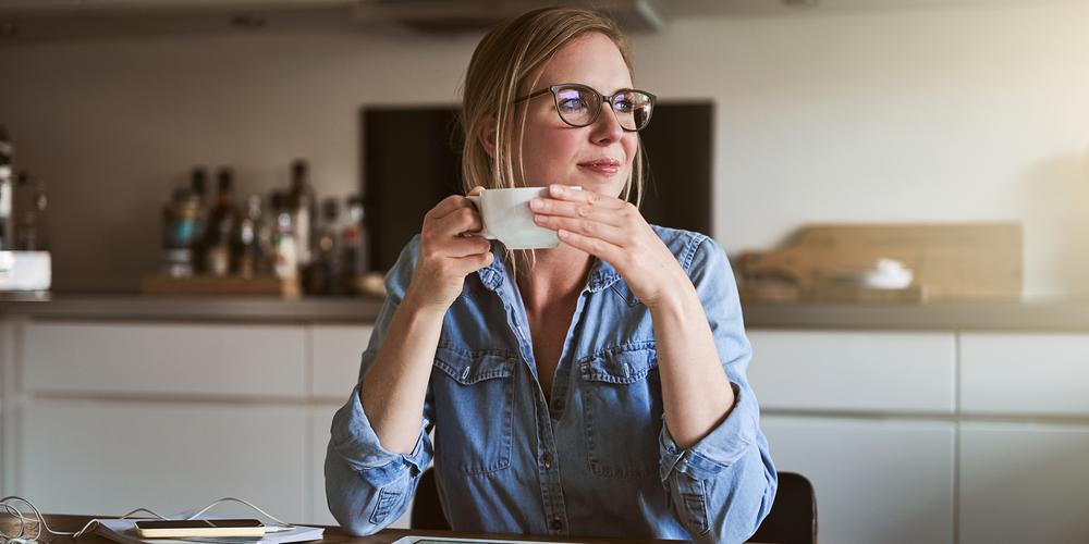 Kvinna vid köksbordet dricker kaffe och tittar tryggt mot fönstret.