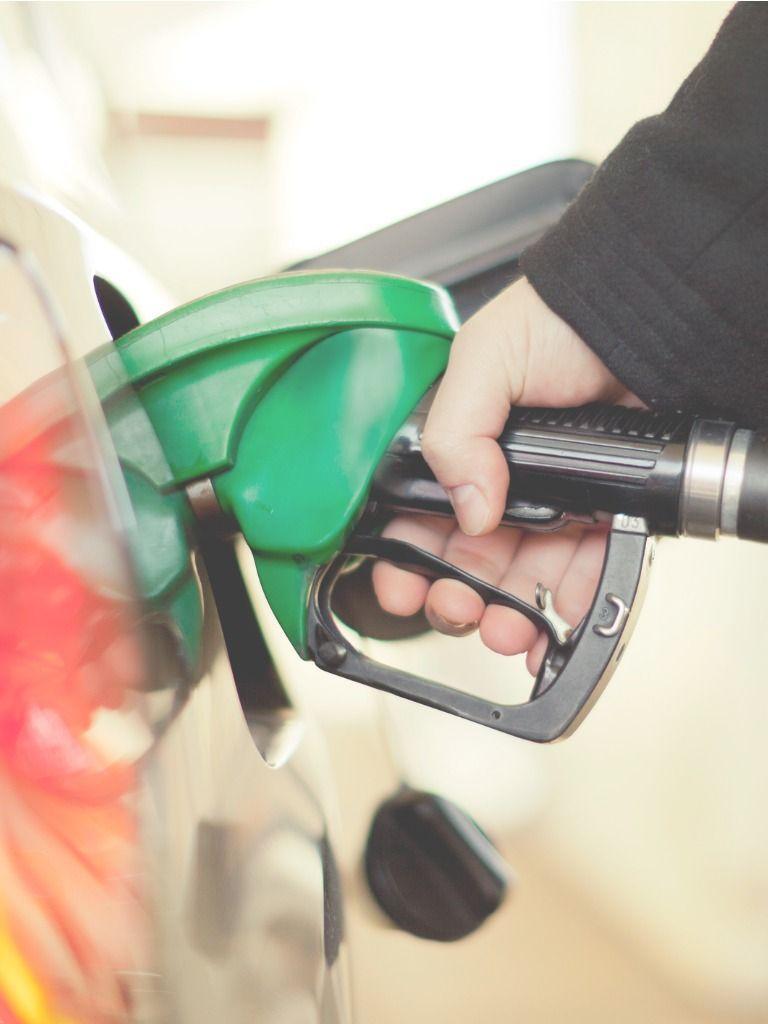 Persona echa gasolina en una gasolinera.