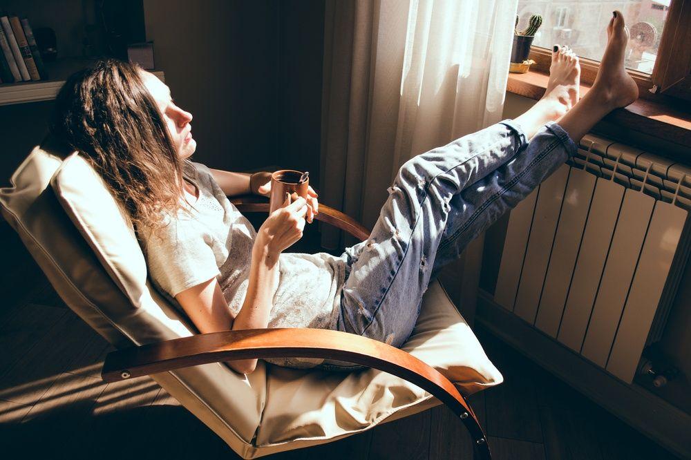 Bilde av en kvinne som sitter i en stol med bena i vinduskarmen