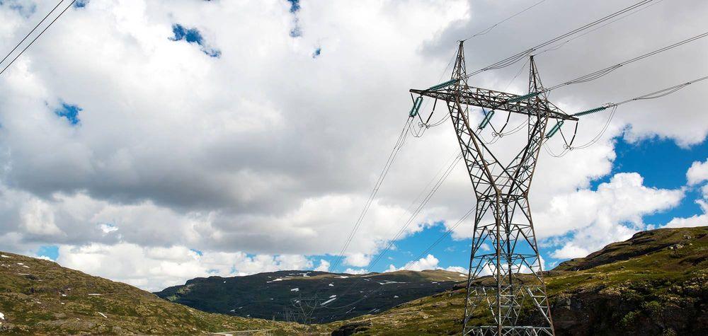 Elektrisitet fraktes via strømmaster i norsk landskap