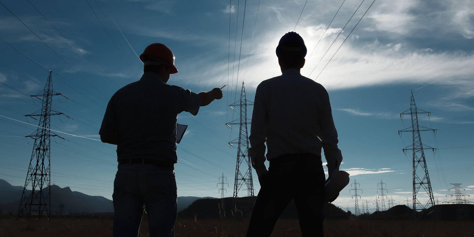 Bilde av to personer som ser på strømmaster i bakgrunnen mens de snakker om dagens strømpris