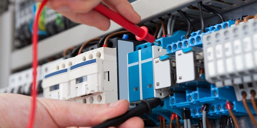 En elektroingeniør gjør tester i sikringsskapet under eltilsyn.