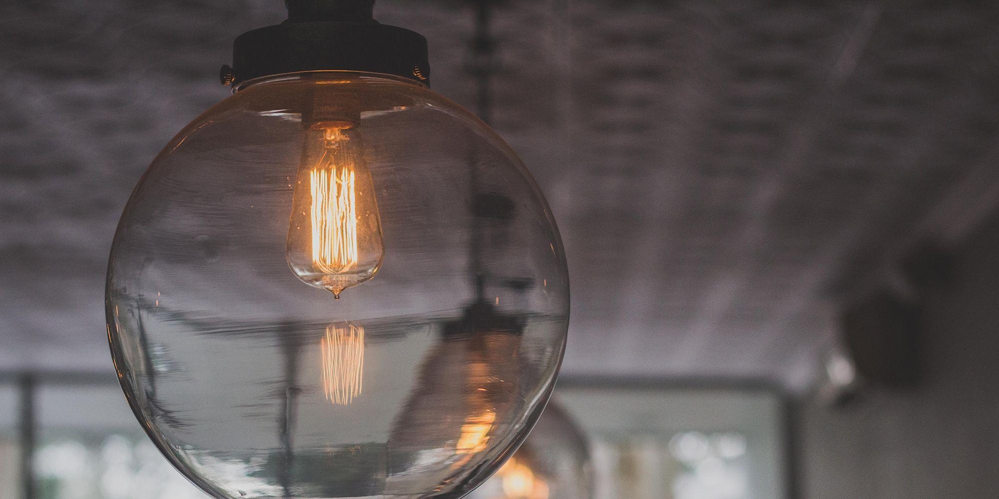 Nærbilde av en lyspære som henger fra et tak