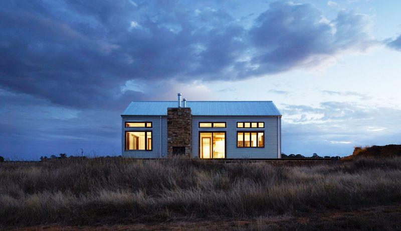 Bilde av et ensomt hus med lys, i mørke omgivelser