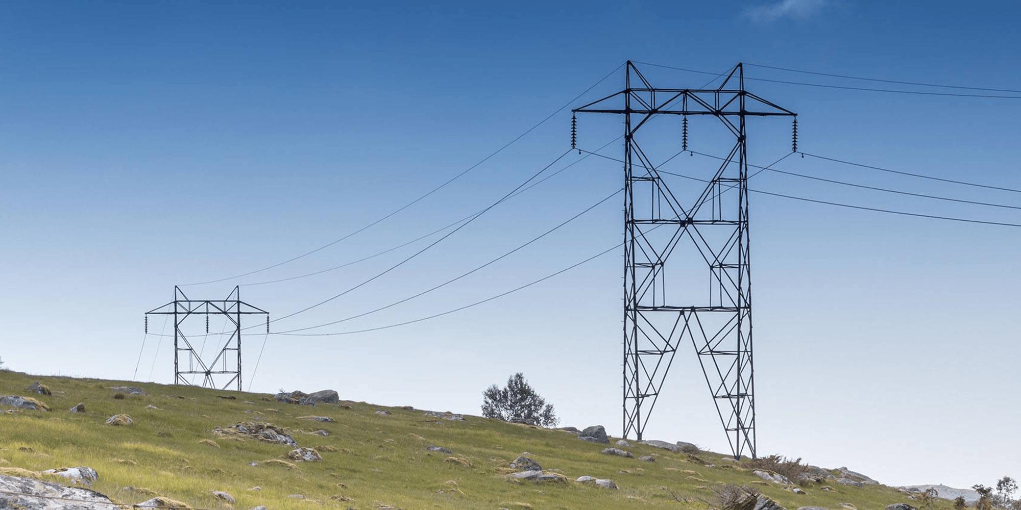 Bilde av strømmaster som strekker seg over et grønt landskap