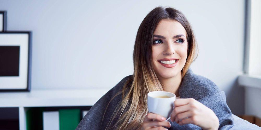 Ung kvinne med kaffekopp sitter under et teppe hjemme i plusshuset sitt