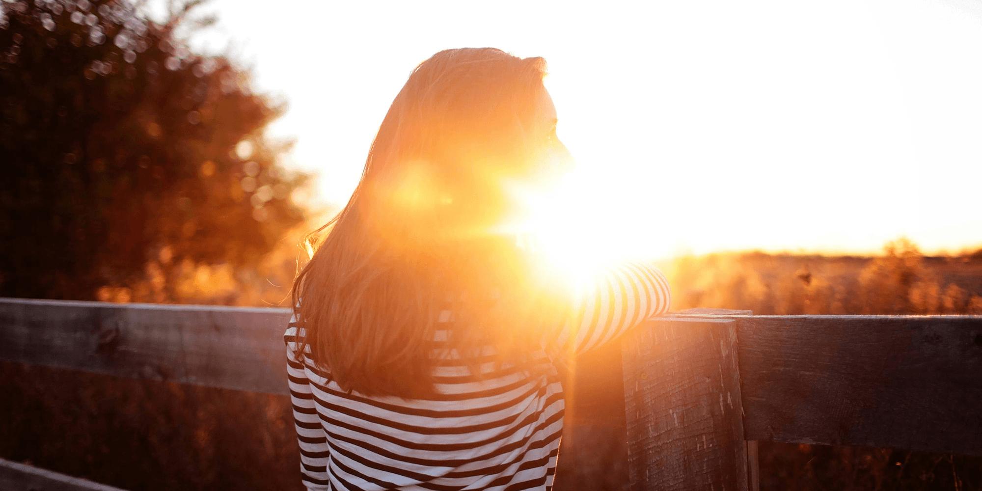 Bilde av en kvinne med ryggen til kameraet i en solnedgang