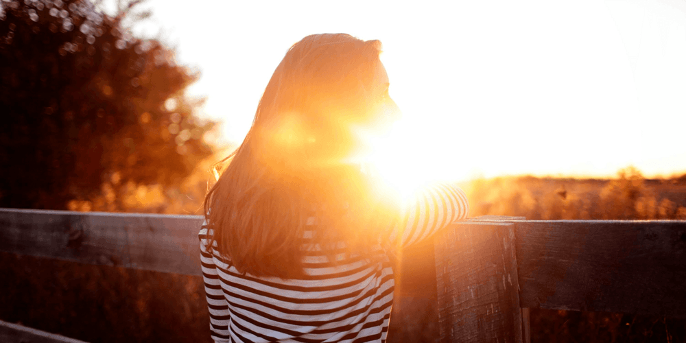 Bilde av en kvinne i en solnedgang med ryggen til