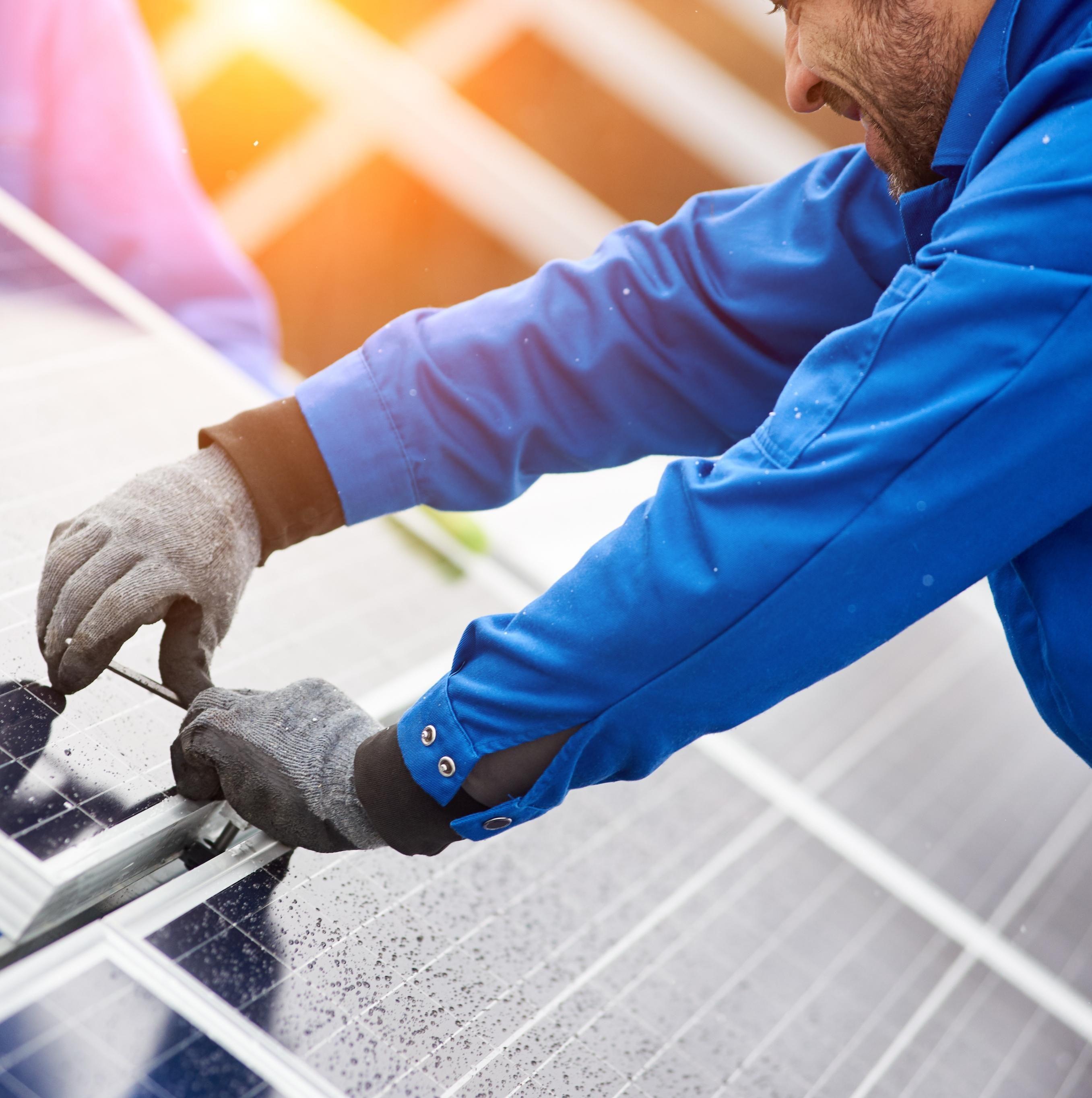 Bilde av en mann som monterer solceller