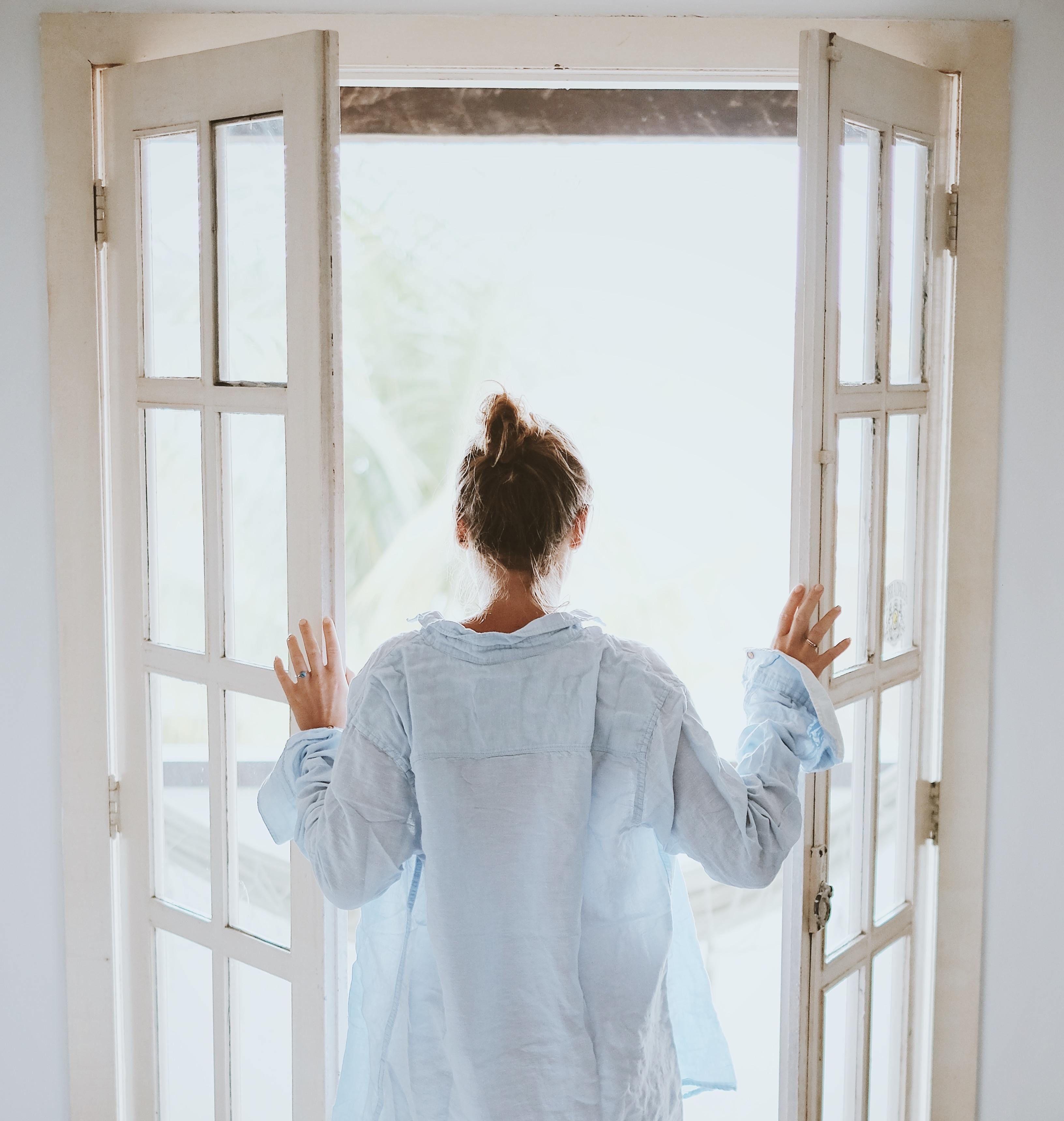 En dame med ryggen til som åpner en dør