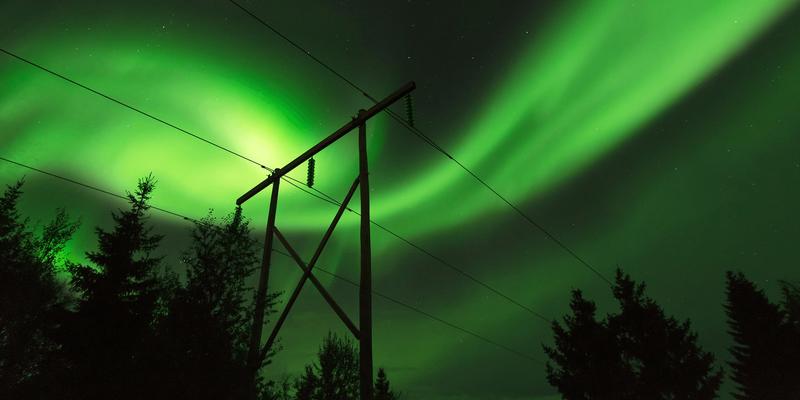 Illustrasjonsbilde: Bilde av en strømmast med nordlys i bakgrunnen