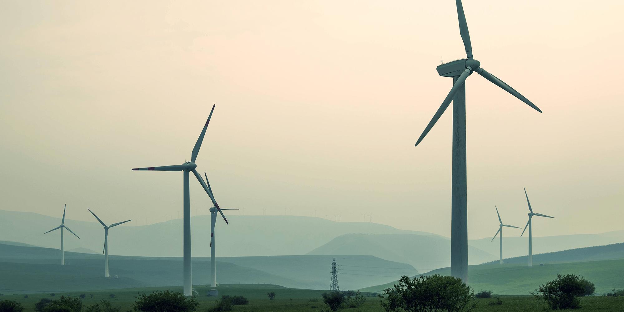 Bilde av vindmøller i et tåkete landskap